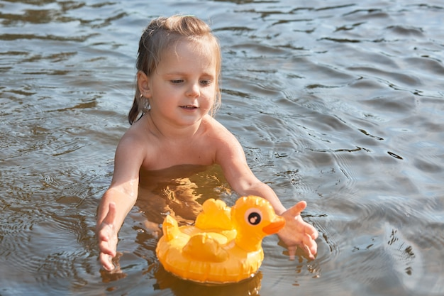 Enthusiastic energetic little kid swimming in water alone, enjoying rest in clean river, spending summer holidays in unity with nature, playing with her toy, having rubber duck on water surface.
