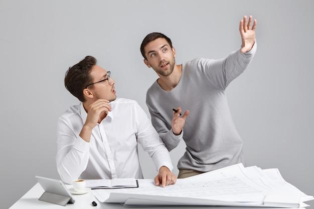 열정적 인 엔지니어가 건설 프로젝트에서 함께 일하며 미래의 계획과 아이디어를 제시하고 싶다고 몸짓으로 표시합니다.