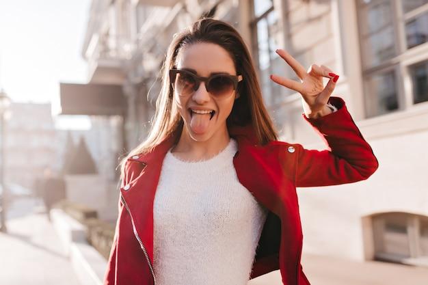 Entusiasta ragazza europea con i capelli scuri in posa con il segno di pace