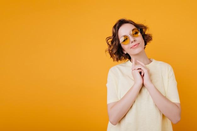 Entusiasta signora europea con acconciatura ondulata alla moda che gode del servizio fotografico sullo spazio arancione
