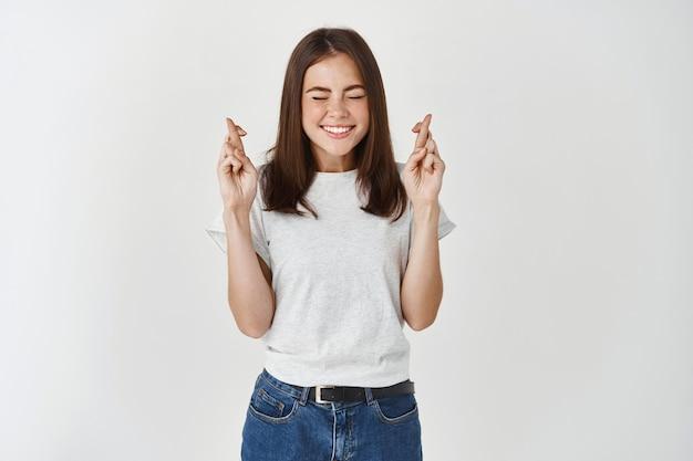 熱狂的で興奮したtシャツを着た魅力的な女性、指を交差させて笑顔で目を期待して、夢が叶い、願い事をし、重要な結果を期待して
