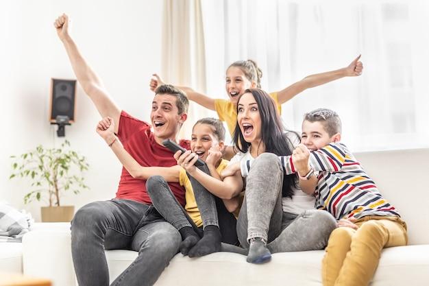 집에서 tv로 스포츠를 보면서 환호하는 5명의 열성적인 가족