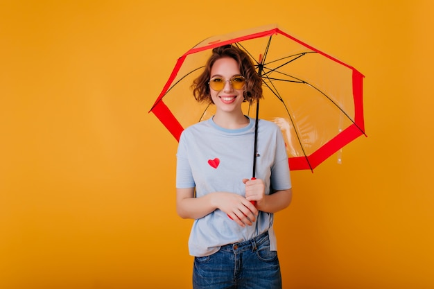 Enthusiastic female model in trendy glasses standing with umbrella and smiling. studio photo of laughing curly european girl with parasol isolated on bright wall.