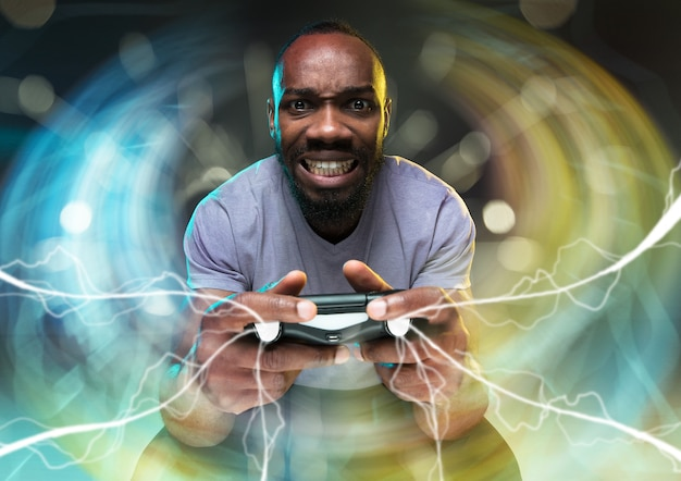 熱狂的なゲーマー。ビデオゲームコントローラーを保持しているうれしそうな若い男