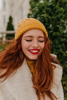 幸せを表現する熱狂的な生姜の若い女性。冬に身も凍る洗練された女の子の屋外写真。
