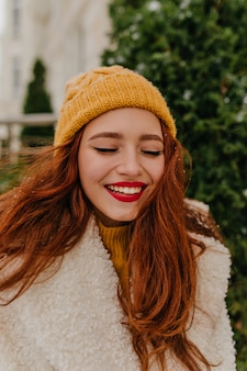 Enthusiastic ginger young woman expressing happiness. outdoor photo of refined girl chilling in winter.