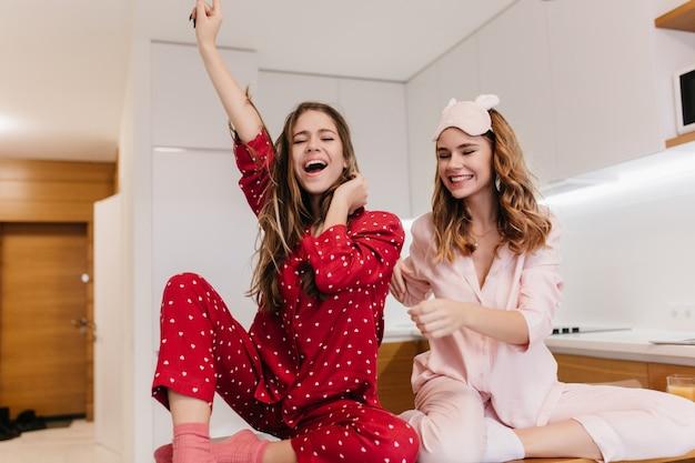 熱狂的な女の子は、ピンクの靴下と明るいパジャマを着て喜んでポーズをとっています。家で朝を過ごす壮大な若い女性の屋内の肖像画。