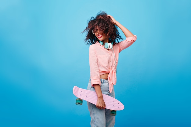 茶色の巻き毛の髪型を楽しんでいる熱狂的な女の子。彼女の髪で遊んで、笑っているスケートボードを持つスリムなアフリカの女の子。