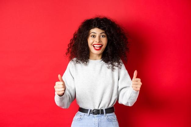 Восторженная девушка с вьющимися волосами и красными губами, показывает палец вверх и говорит да, согласен с вами, делает комплимент за хорошую работу, как что-то крутое, стоит на стене студии