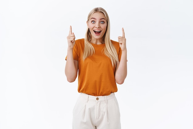 Enthusiastic good-looking blond woman in orange t-shirt, tattoos on arms, smiling wondered and amused, look surprised, pointing fingers up astonished, react joyfully to wonderful event