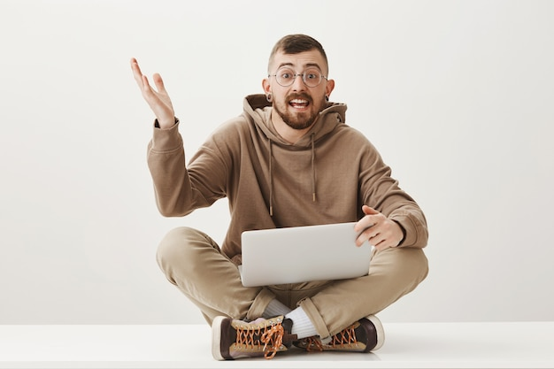 Enthusiastic guy discuss something while sitting on crossed legs with laptop