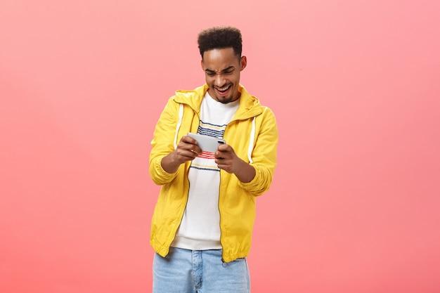 ピンクの背景の上でインターネットで自由な時間を過ごす情熱とスリルでデバイスの画面を見つめている両手で携帯電話を持って素晴らしいスマートフォンゲームを楽しんでいる熱狂的な男