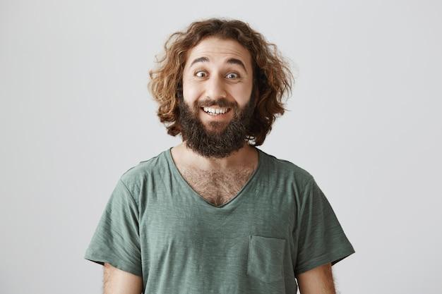 Ragazzo barbuto mediorientale bello entusiasta che sorride