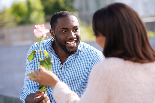 Enthusiastic handsome pleasant guy making his girlfriend smile while surprising her with little gift during their causal date