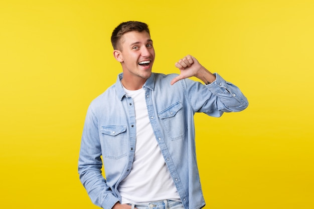 Восторженный красивый улыбающийся блондин со счастливой ухмылкой, указывая на себя как на волонтер, говорит о личных достижениях и целях, хочет участвовать, желтый фон.