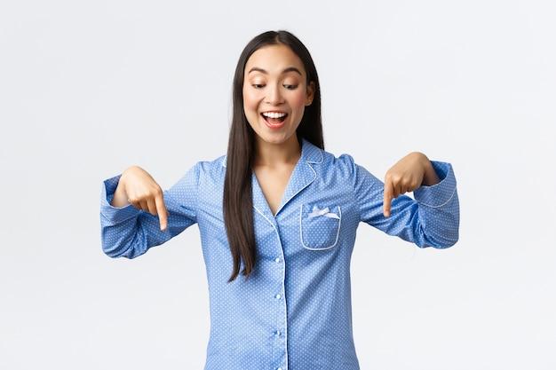 열정적 인 행복 아시아 소녀는 멋진 뉴스에 반응하고 파란색 잠옷을 입고 손가락을 아래로 가리키며 기뻐하고 흥미롭고 쾌활한 미소를 지으며 훌륭한 프로모션 할인, 흰 벽을보고