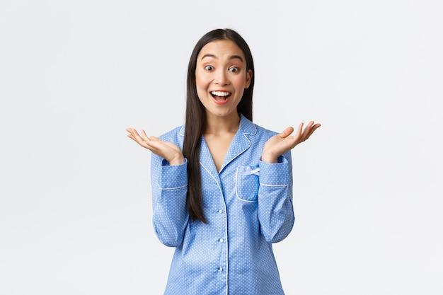 青いパジャマを着た熱狂的な幸せな美しいアジアの女の子は、素晴らしいアイデアを聞き、手をたたき、素晴らしいアドバイスを聞いて驚いているように見えます。ジャマでガールフレンドと寝坊を楽しんでいる女性。