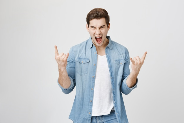 Enthusiastic happy man having fun, show rock-n-roll gesture