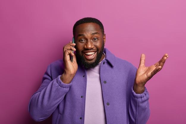 Un uomo felice ed entusiasta parla tramite telefono cellulare, ha ricevuto una chiamata da un amico o un collega, discute di buone notizie, alza la mano, racconta qualcosa di emotivo