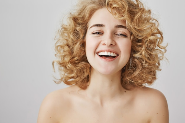 Enthusiastic happy woman with naked shoulders laughing and smiling