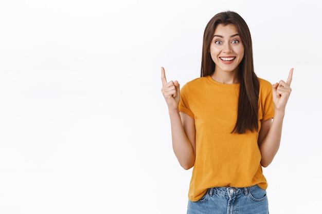 Entusiasta, impressionata ed emozionata sorridente, felice donna bruna in maglietta gialla, ridendo e sorridendo entusiasta, non vedo l'ora di provare un'incredibile proposta di vendita, indicando una bella pubblicità