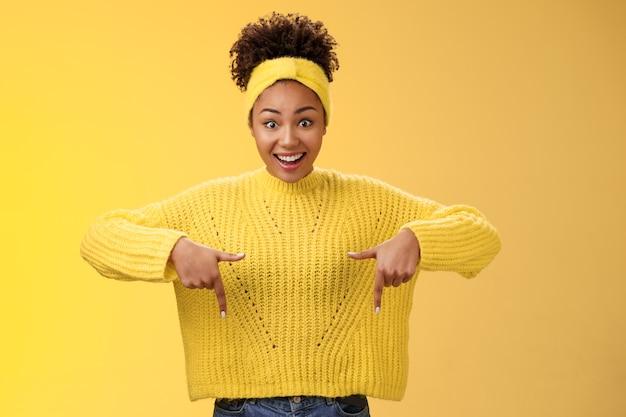 Восторженно впечатлила удивленная красивая афро-американская женщина с широко раскрытыми глазами, опущенная челюсть, улыбаясь, задыхаясь, удивленно указывая вниз, удивленно стоя на желтом фоне, демонстрируя удивительную возможность.