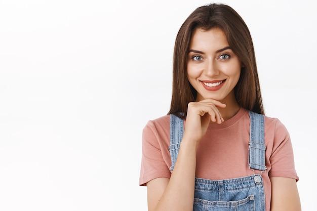 Восторженная, заинтригованная красивая женщина выслушивает интересную идею, довольно улыбается, согласно кивает, одобряет потрясающий план, задумчиво трогает подбородок, стоит на белом фоне и думает