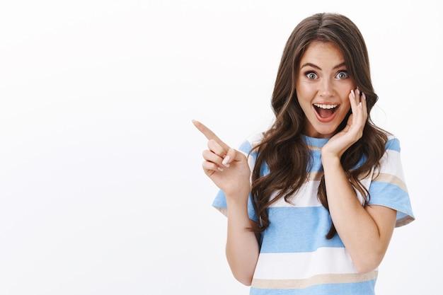Entusiasta gioiosa donna sorpresa presenta un'offerta incredibile, puntando il dito a sinistra spazio copia, sorridendo gioiosamente e impressionato guarda la macchina fotografica, tocca la guancia stupita, muro bianco