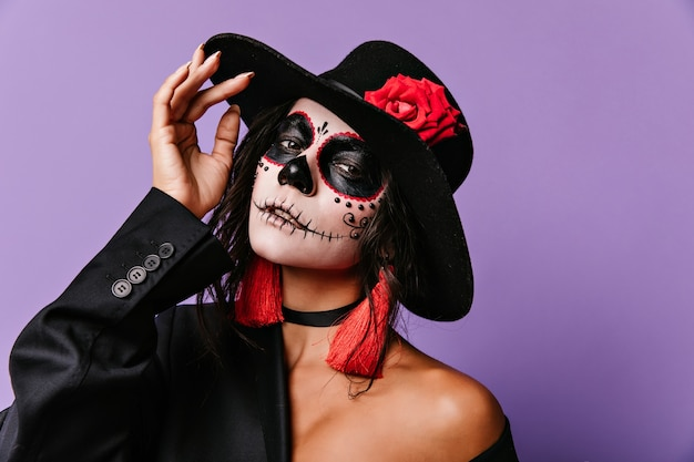 Enthusiastic latin lady in muertos outfit. indoor photo of inspired caucasian girl wears zombie costume in halloween.