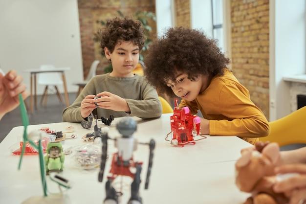 아프리카 머리를 가진 열정적인 어린 소년이 전자 장난감 키트를 조립하면서 웃고 있습니다.