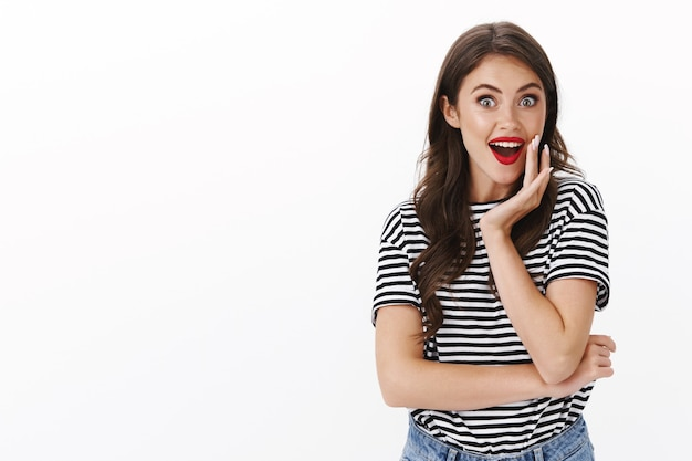 Entusiasta vivace donna divertita ascolta pettegolezzi, sorride divertita e gioiosa, ansima sorpresa, guarda la telecamera gioiosa, reagisce affascinata scopri un meraviglioso fantastico promo, muro bianco