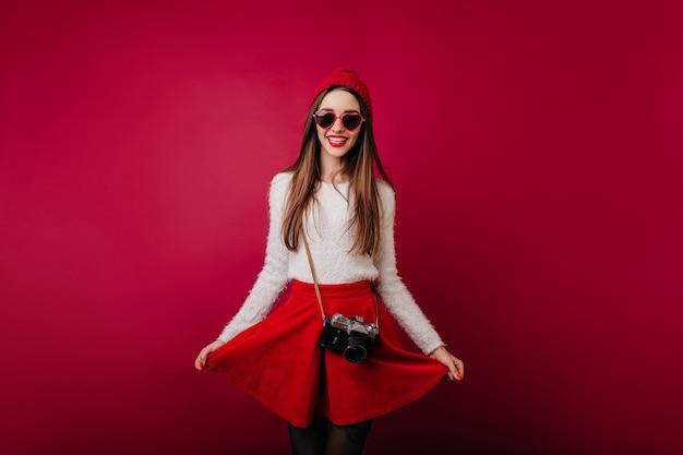 Fotografo femminile dai capelli lunghi entusiasta che gioca con la gonna rossa