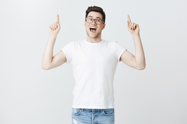 Enthusiastic male student in glasses inviting to event, pointing fingers up