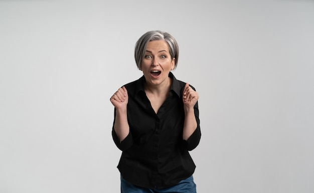 Enthusiastic mature woman with open mouth rejoices in gain