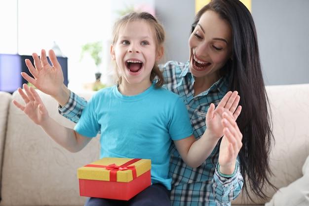 열정적 인 엄마와 딸 선물 상자가 소파에 앉아있다