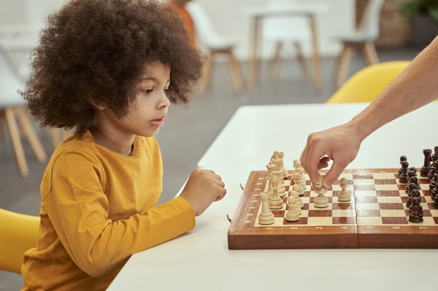 Enthusiastic player cute little clever boy thinking while playing chess with adult sitting at the