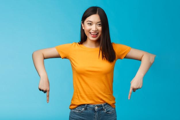 Восторженная приятная азиатская белокурая современная студентка приглашает вас на потрясающее мероприятие, указывая вниз, указывая на нижнюю рекламу, стоять на синем фоне, широко улыбаясь, счастливо смотреть в камеру.