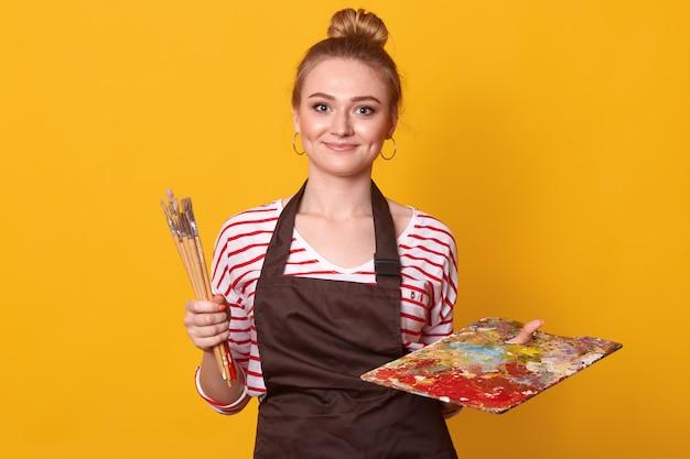 Восторженный позитивный художник с булочкой на голове, держа в одной руке грязную палитру и набор художественных кистей