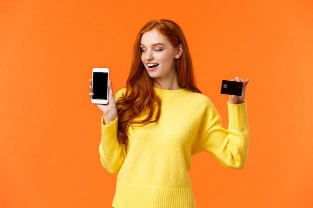 Восторженная симпатичная современная рыжая женщина, рекламирующая мобильный банкинг, делающая покупки онлайн