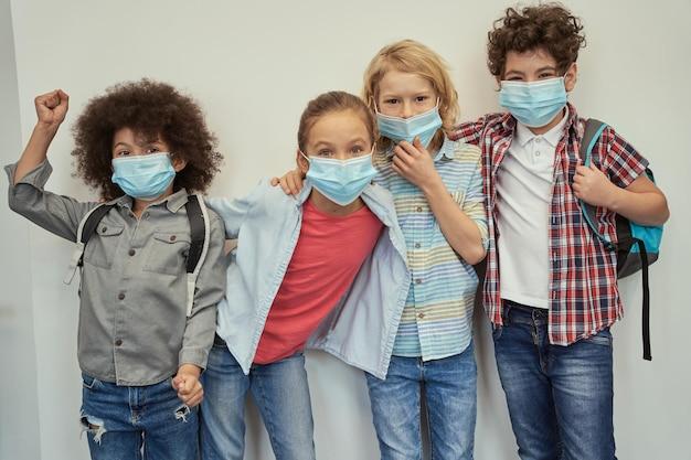 카메라 포즈를 보고 있는 보호용 안면 마스크를 쓰고 다양한 아이들을 매료시키는 열정적인 학생들