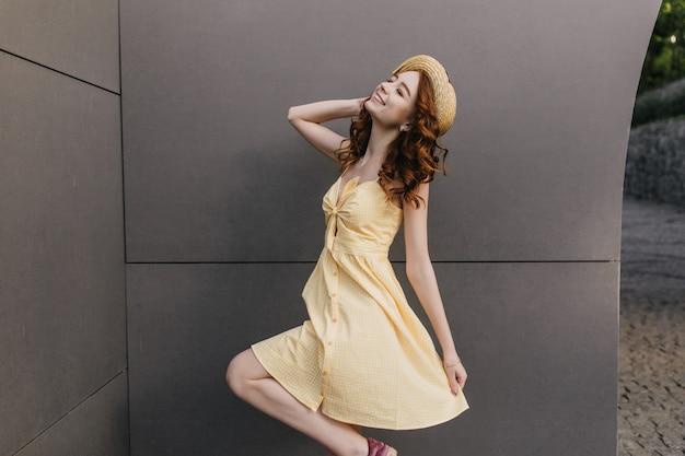 Восторженная рыжеволосая девушка танцует в винтажной соломенной шляпе на серой стене. фото радостной кудрявой дамы в желтом наряде в помещении.