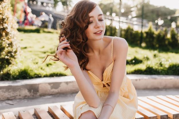 공원에 앉아있는 동안 뭔가에 대해 생각하는 열정적 인 red-haired 소녀. 화창한 아침에 포즈를 취하는 물결 모양의 생강 머리를 가진 영감을 유럽 여성의 야외 촬영.
