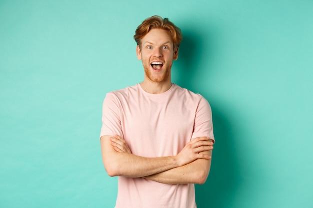 티셔츠를 입은 열정적인 빨간 머리 남자는 흥미로운 프로모션을 확인하고, 가슴에 팔짱을 끼고, 경외심으로 카메라를 바라보고, 청록색 배경 위에 서 있습니다.