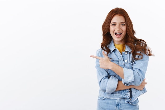 Восторженная нахальная красивая рыжая девушка с веснушками в джинсовой куртке, указывающая пальцем влево, веселая и радостная улыбающаяся, демонстрирующая отличное пространство для копирования, продвигающая продукт с довольной улыбкой