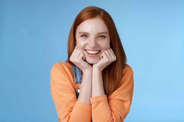 Восторженная нахальная симпатичная рыжая кавказская девушка худощавая голова ладони выглядит удивленно заинтригованно слушать интересную историю приятно улыбается смеется глупые шутки стоя синий фон взволнованный счастливый