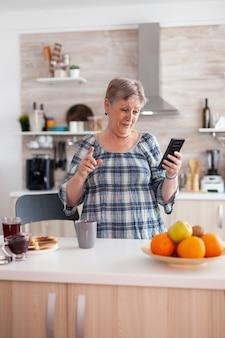 朝食時にキッチンに座って笑っている家族と一緒に携帯電話のウェブカメラで話す熱狂的な年配の女性。現代のスマートフォンインターネット技術を使用した本物の高齢者。