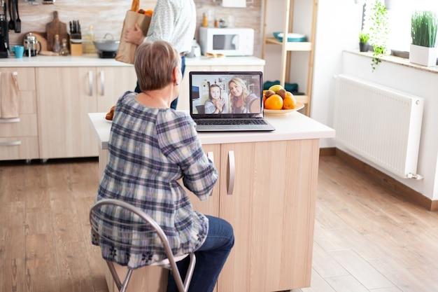 キッチンに座っているビデオ会議中にラップトップのウェブカメラを使用してオンラインで家族と話している熱狂的な年配の女性。現代のインターネット技術を使用した娘と姪、おばあちゃんとのビデオ通話。
