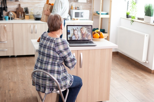 Enthusiastic senior woman talking with family online using laptop webcam during a video conference sitting in kitchen. videocall with daughter and niece, grandma using modern internet techonolgy.