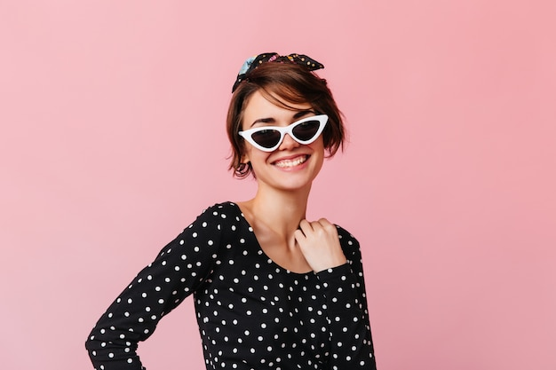 Enthusiastic short-haired woman posing in sunglasses
