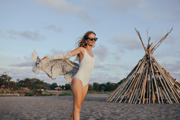 Enthusiastic slim woman in sunglasses enjoying sea breeze.